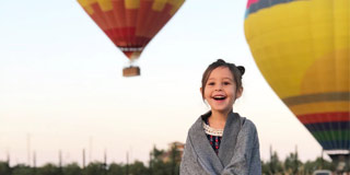 Girl standing in front of hot air balloons