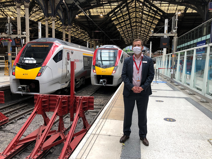 Man wearing a face covering whilst standing in front of trains
