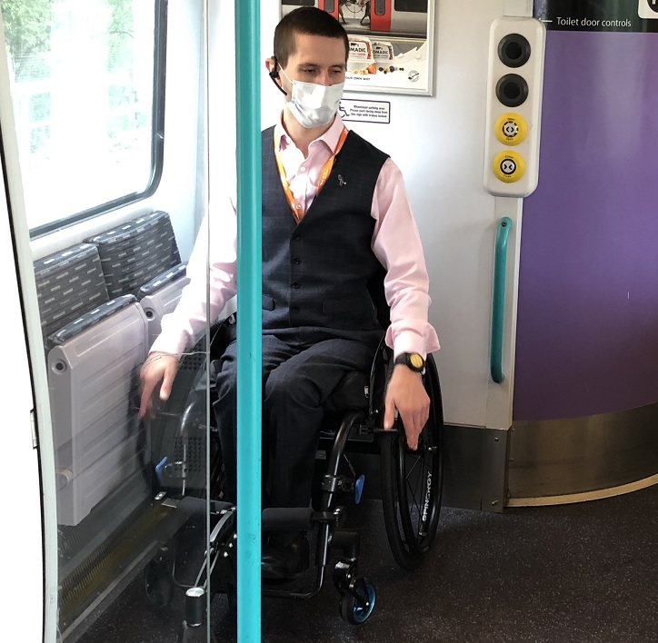 Train passenger in a wheelchair in a wheelchair space on a train, wearing a face covering.