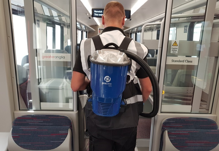 A person wearing a backpack vacuum cleaner on a train.