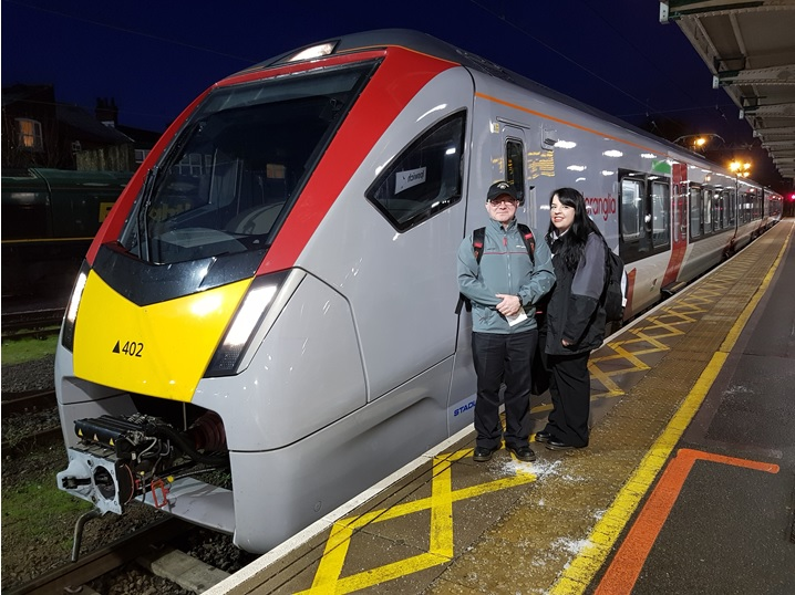 Image of two Greater Anglia Traincrew next to bi-mode train