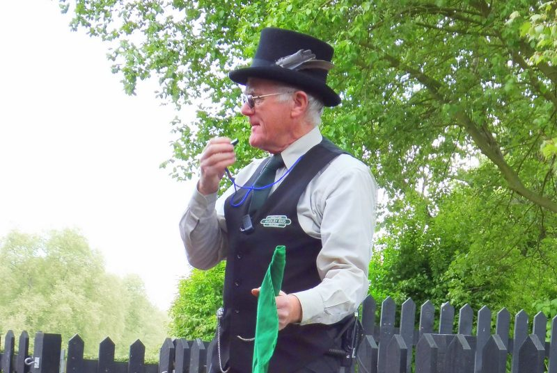 A man in train garb blowing a whistle