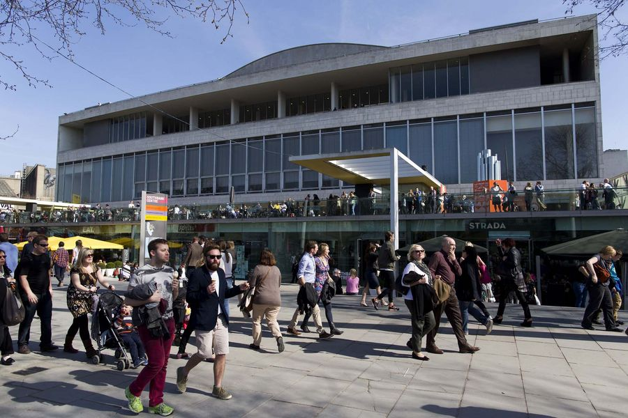 People enjoy sunny weather as they walk along the South Bank in London