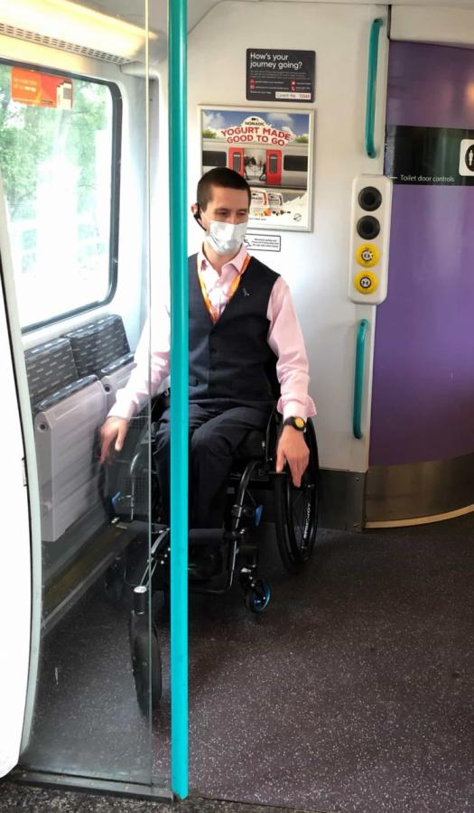 Man wearing a blue face covering sitting in wheelchair on a train