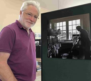 Norwich based photographer David Pearce standing with his Departures Exhibition Courtesy Lowestoft Central Project