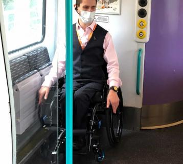 Man in a wheelchair wearing a face covering, waiting on the train