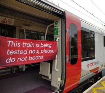 A train with open doors and a red banner saying 'this train is being tested now, please do not board.'