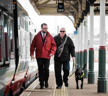 Member of staff walking with blind man and dog