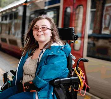 Disabled woman in a wheelchair, smiling at camera with a train in the background