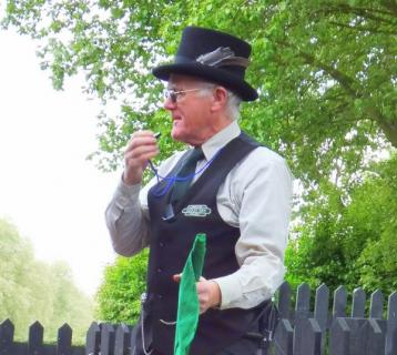A man in a top hat with a whistle